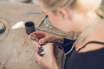 High angle view of woman carving ceramic at table in workshop