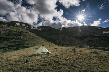 Tent on mountain against cloudy sky during sunny day