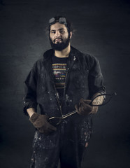 Portrait of craftsman holding tongs while standing against black background