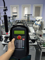 Focus on control panel. Male hand is holding the control panel of the industrial plant and pushing the button.  Industry 4.0 concept.