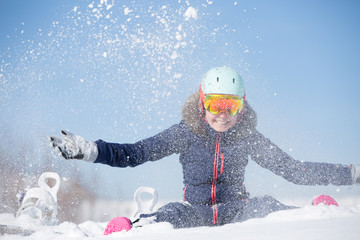 Image of sports woman sitting in snowdrift, snow-throwing