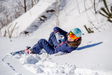 Photo from back of athlete in helmet lying on snowy slope