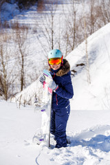 Photo of athlete in helmet with snowboard standing in park