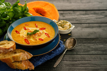 Delicious homemade pumpkin soup with prawns, chili and basil leaves on the wooden background. Copyspace.