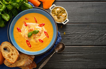Delicious homemade pumpkin soup with prawns, chili and basil leaves on the wooden background. Copyspace. Top view.