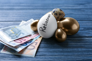 Egg with word RETIREMENT and money on table. Pension planning