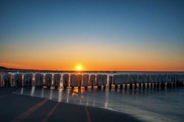 Sunrise, sunset of a beautiful winter landscape with frozen wooden breakwater. Concept holidays and travel
