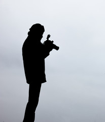Silhouette of a photographer like to travel and photography, looking pictures in his camera