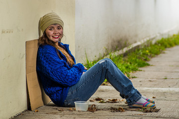 Outdoor view of homeless smiling woman begging on the street in cold autumn weather sitting on the floor at sidewalk