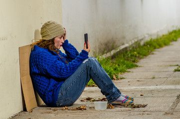 Outdoor view of homeless woman begging on the street in cold autumn weather sitting on the floor at sidewalk with a cellphone in her hand