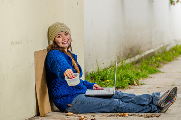 Outdoor view of homeless smiling woman begging on the street in cold autumn weather sitting on the floor with a empty plastic flask and computer over her legs, at sidewalk