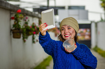 Outdoor view of homeless woman on the street in cold autumn weather holding an empty plastic flask in her hand taking a selfie with a tablet at sidewalk