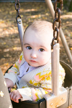 Close-up of a baby girl sitting on swing