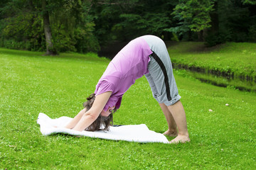 woman in her 50s doing yoga in a park