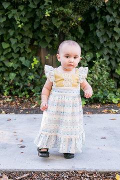 Portrait of cute little baby girl standing on sidewalk
