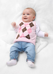 Funny cute female newborn dressed in pink sweater and jeans on white fur blanket. Infant baby girl with pink sweater and jeans.