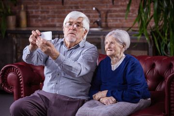 Senior couple taking selfie on smart phone while sitting on couch