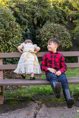 boy and baby sister on park bench
