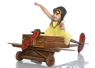 Little girl in the cap of the pilot