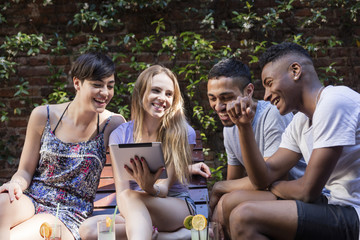 Multi-ethnic group of friends relaxed and using the tablet outdoors