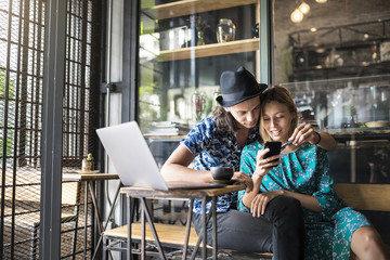 Artist couple sitting in cafe and checking the young woman's smartphone