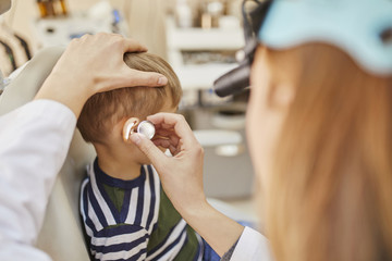 ENT physician examining ear of a boy