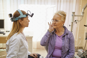 ENT physician talking to senior woman in medical practice
