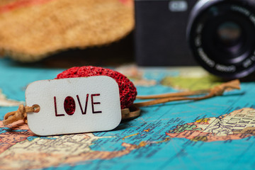 Travel concept background .A love sing on a map with a retro camera and a hat on the background