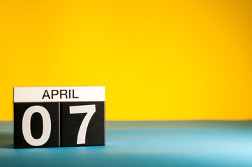 April 7th. Day 7 of april month, calendar on table with yellow background. Spring time, empty space for text