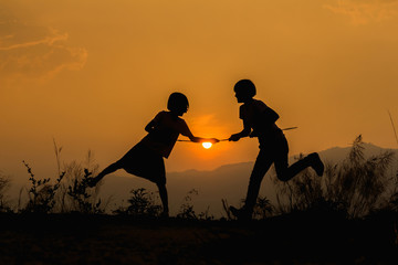 Silhouette happy two little girl playing at sunset background