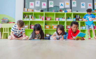 Group of diversity kid lay down on floor and reading tale book in preschool library,Kindergarten school education concept