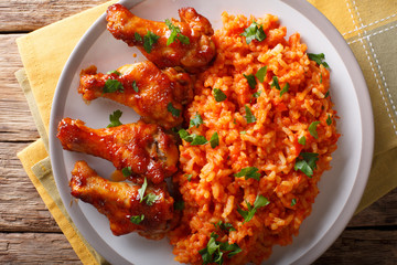 Classic Nigerian Jollof Rice with fried chicken wings close-up. horizontal top view