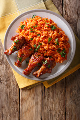 Nigerian food party: Jollof rice with fried chicken wings close-up. Vertical top view