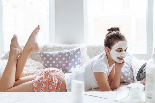 Girl making clay facial mask