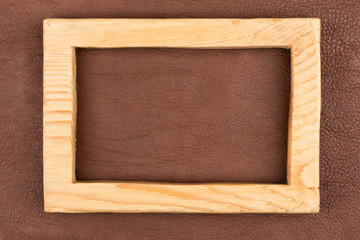 Rectangular frame made from light wood lies on brown natural leather. Texture of a tree.