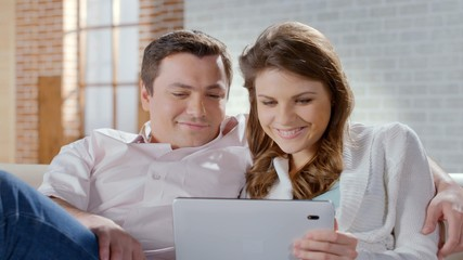 Excited wife and husband looking at tablet, shopping online, family business