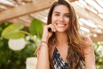 Brunette smiling female sits in outdoor cafeteria, has broad smile, has good rest, has satisfied expression, rests in tropical resort country. Cute young woman rests in terrace cafe. Positiveness
