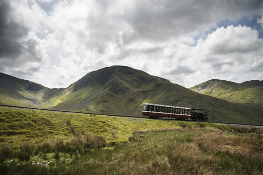 Snowdon Mountain Railway making it's way up to Snowdon with Moel Cynghorion in background landscape