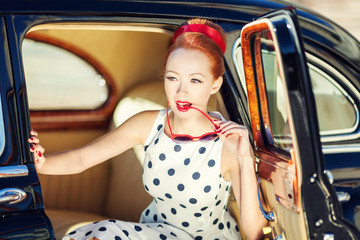 Beautiful girl in retro style and a vintage car