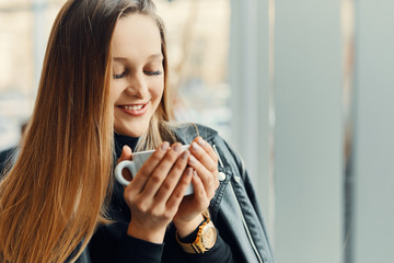 Pretty girl stand near the window with cup of coffee and smile