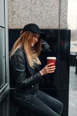 Young girl stand near the wall wear hat and glasses and drink coffee from red cup