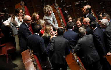 President of Fratelli d'Italia party (Brothers of Italy) Giorgia Meloni talks on the phone surrounded by deputies at the Chamber of Deputies during the second session day since the March 4 national election in Rome