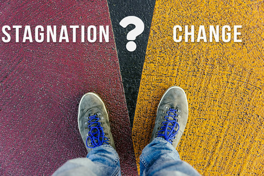 Concept of facing a crucial decision about stagnation and change shown by shoes on different colored pathways