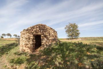 Landscape with construction for agricultural use. Stonecraft, Barraca de vinya, or caseta de pedra seca. Typical mediterranean rural structure. Sant Fruitos del Bages,Catalonia,Spain.