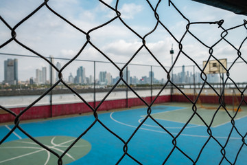 basketball court behind fence with city skyline background