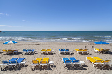 Mediterranean beach and sunbeds in Sitges,Catalonia,Spain.