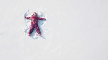 Child girl playing and making a snow angel in the snow. Top flat overhead view