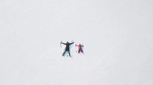 Child girl playing and making a snow angel in the snow with her mother . Top flat overhead view