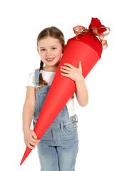Hübsches kleines Mädchen mit Zöpfen hält eine Einschulungstüte in den Händen und lacht