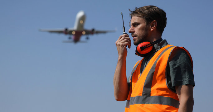 Airport Ground Worker Man Communicating Over Walkie Talkie with Air Traffic Control about Airspace Security Using Telecommunication Equipment while Airplane Flying Over Head